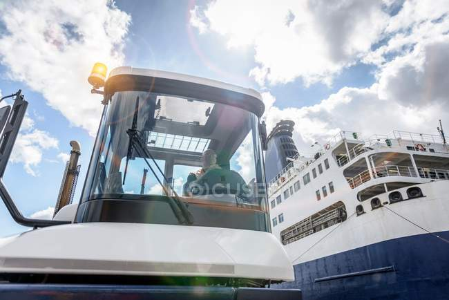 Shipping container truck and driver with ship in port, low angle view — Stock Photo
