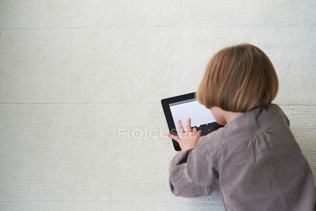 Girl lying on floor using digital tablet — Stock Photo