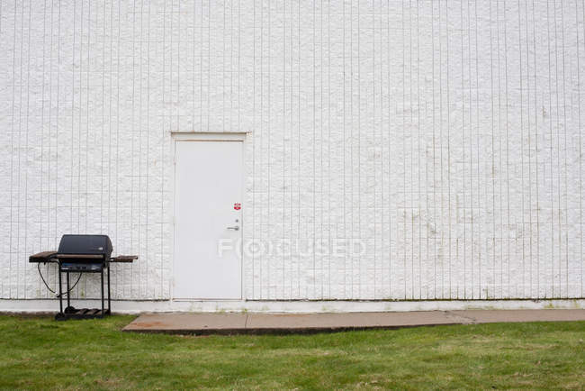 Barbacoa en césped verde por la pared del edificio blanco - foto de stock