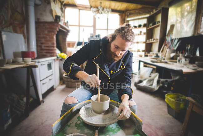 Bearded mid adult man in workshop sitting at pottery wheel using diddler to make clay pot — Stock Photo