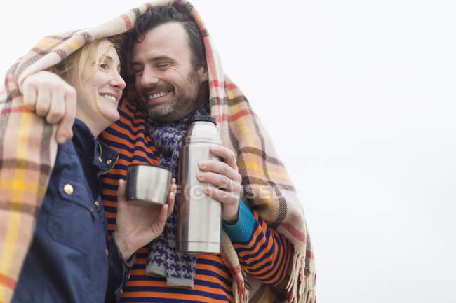 Paar trinkt unter Decke Heißgetränk aus Thermoskanne — Stockfoto