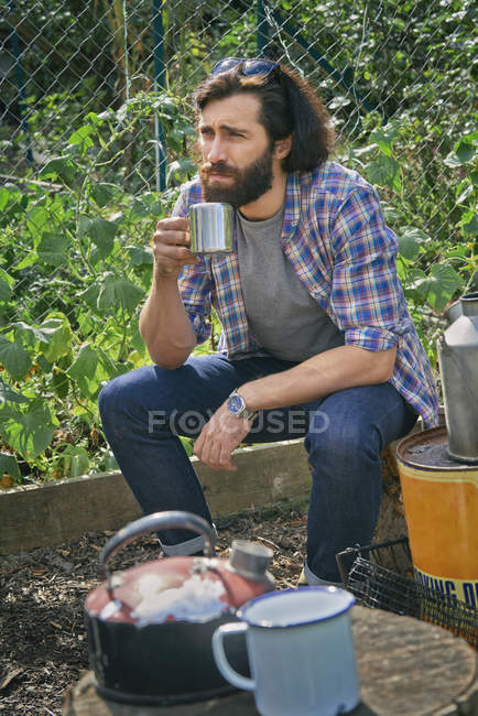 Mid adult man taking a coffee break on allotment — Stock Photo