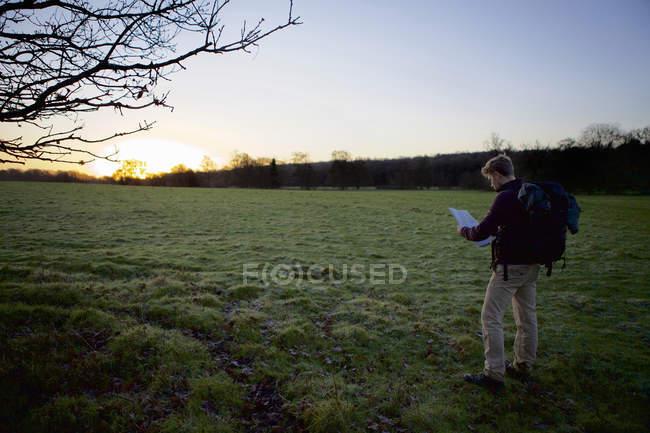 Randonneur masculin lisant la carte dans le champ au coucher du soleil — Photo de stock