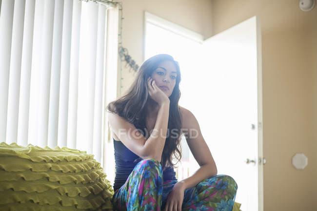 Молодая женщина, сидящая на локти, руку на подбородок, глядя — стоковое фото