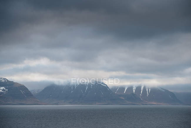 Mountains across water with low clouds — Stock Photo