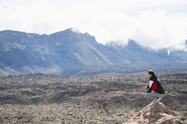 Mid adult man crouching on rock, Teide National Park — Stock Photo