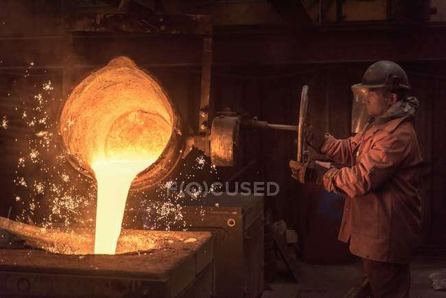 Worker pouring molten metal from flask in foundry workshop — Stock Photo