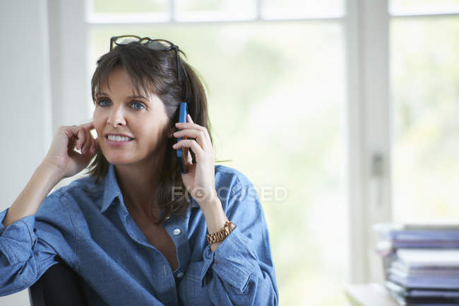 Femme mûr répondant sur l'appel téléphonique et l'oreille de fermeture — Photo de stock