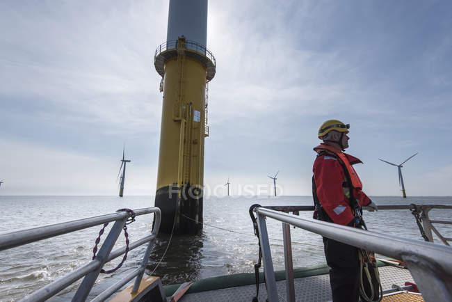 Инженер готовится к восхождению на ветрогенератор на оффшорной ветроэлектростанции — стоковое фото