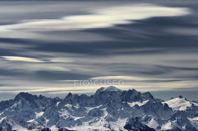 Turva as nuvens acima de montanhas cobertas de neve, longa exposição tiro — Fotografia de Stock