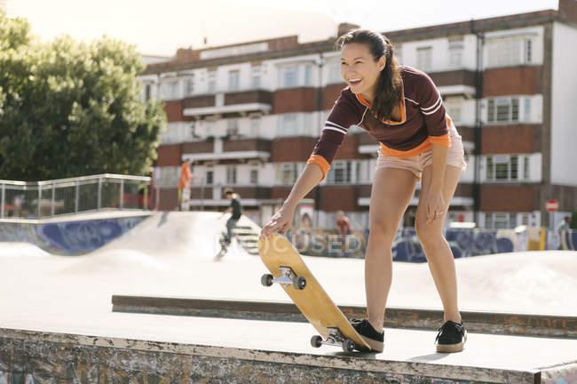 Weibliche Skateboarder Vorbereitung auf Skateboardrampe — Stockfoto