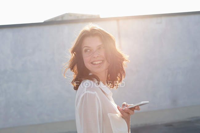 Portrait of young woman holding cell phone in sunlight — Stock Photo
