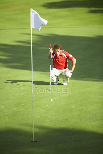 Frontansicht des Golfspielers, der sich vor der Golffahne kauert und über Strategie nachdenkt — Stockfoto