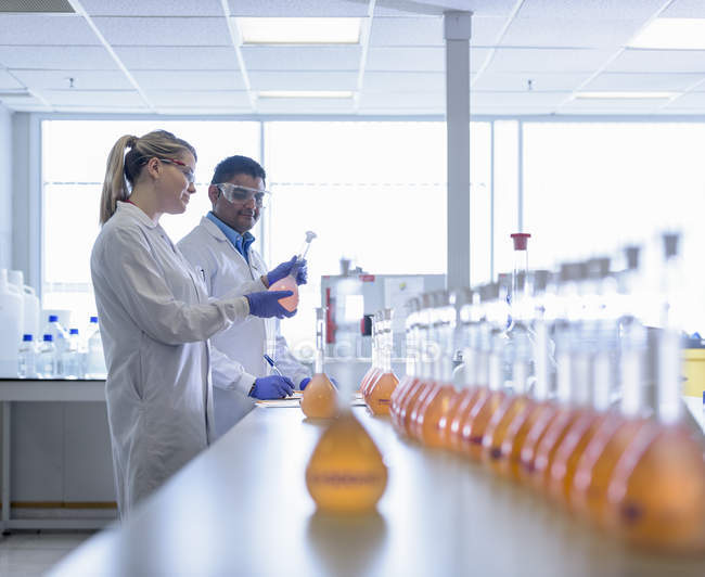 Laboratory chemists inspecting food colouring in laboratory — Stock Photo