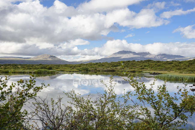 Blue cloudy sky reflecting in lake water, Thingvellir, Iceland — Stock Photo