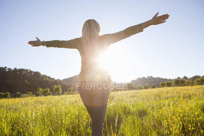 Rear view of mature woman with arms open in meadow at sunset — Stock Photo