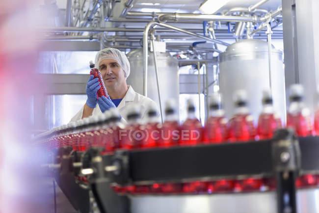 Працівник інспекційних пляшки води на лінії з виробництва навесні водяний завод — стокове фото