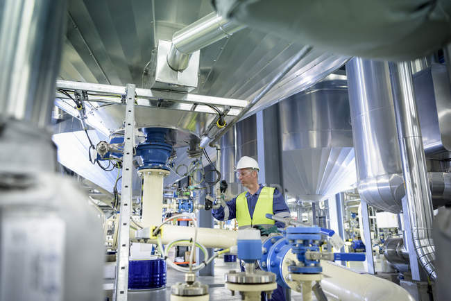 Worker with process machinery in oil blending factory — Stock Photo