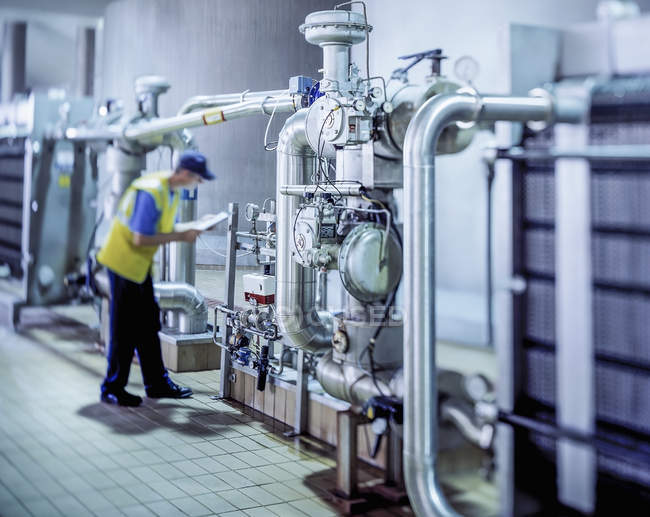 Worker inspecting water filtration in brewery — Stock Photo