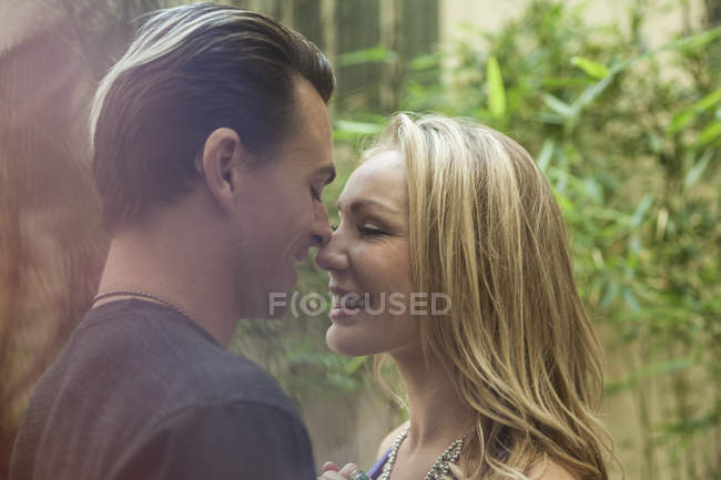 Young romantic couple, face to face, smiling, outdoors — Stock Photo