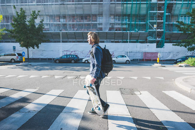 Young man crossing pedestrian crossing with skateboard — Stock Photo