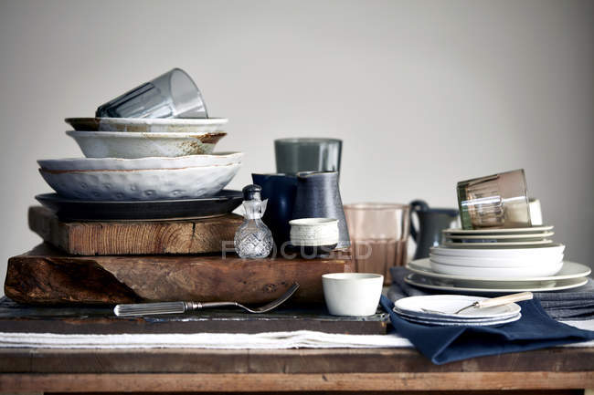 Stacked crockery stacked on cutting board for washing up — Stock Photo