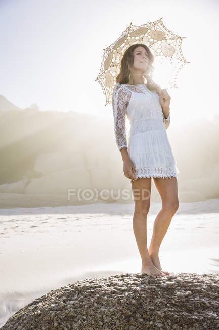 Woman on beach standing on rock wearing short white dress holding umbrella, looking away — Stock Photo