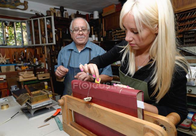 Старший чоловік дивляться стажист застосування сусальне золото до книги хребта в традиційних палітурне майстерні — стокове фото