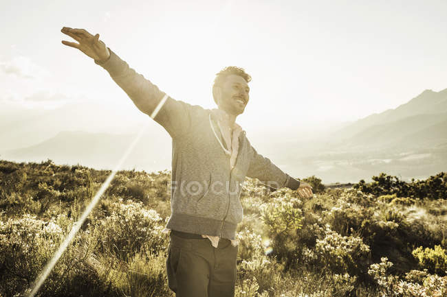 Man in field, arms open smiling — Stock Photo