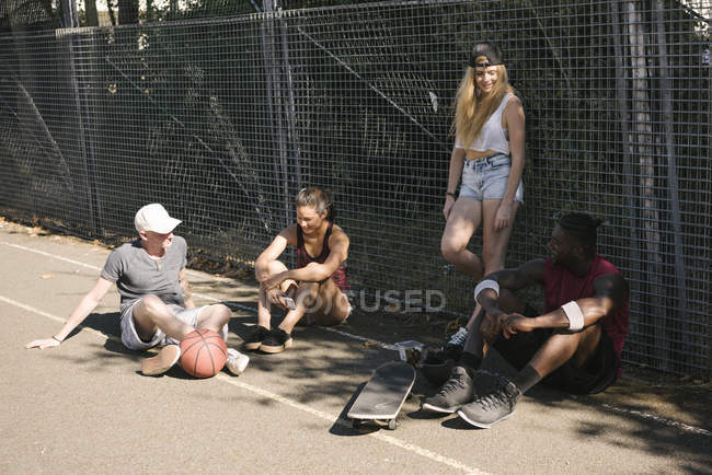 Four adult skateboarder friends sitting chatting on basketball court — Stock Photo