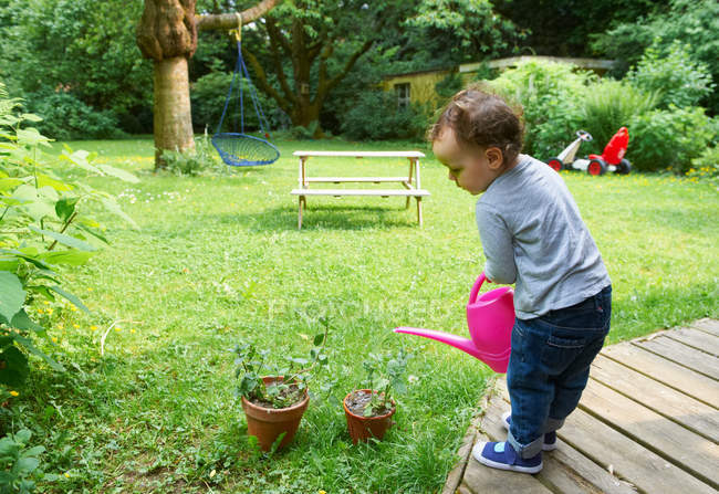 Toddler boy watering plants in backyard — Stock Photo