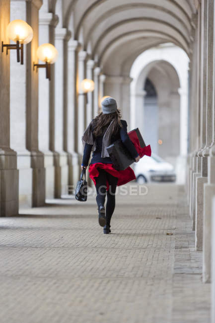 Rear view of mature woman with Christmas gift walking through city  colonnade — Stock Photo
