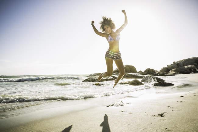 Прыгающая женщина на пляже — стоковое фото