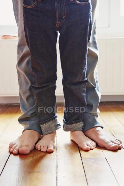 Descalzos padre e hijo de pie en el suelo - foto de stock