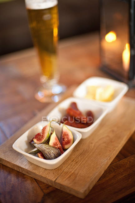 Bowls of fruit and cheese on table with flaming candle on background — Stock Photo
