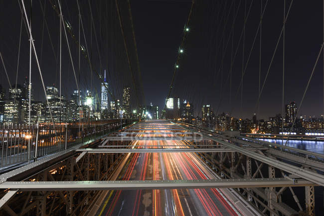Elevated view of traffic light trails crossing Manhattan Bridge at night, New York, USA — Stock Photo