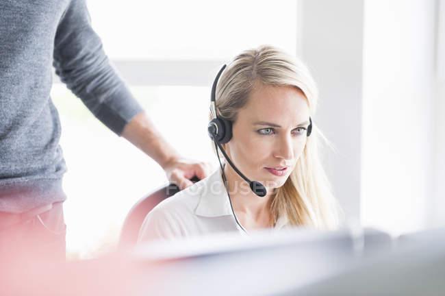 Femme utilisant le casque tout en s'asseyant avec l'homme restant dans le bureau — Photo de stock