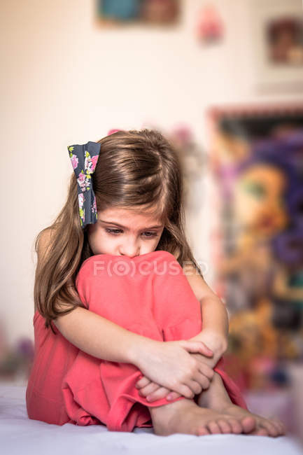 Sad girl hugging knees — Stock Photo