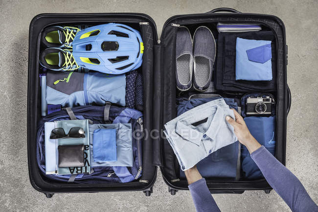 Overhead view of man's hands packing suitcase with walking boots, bike helmet, backpack, retro camera and blue shirt — Stock Photo