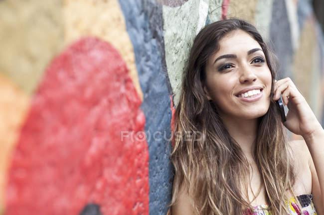 Retrato de mujer joven, apoyado contra la pared, usando teléfono móvil, sonriendo - foto de stock
