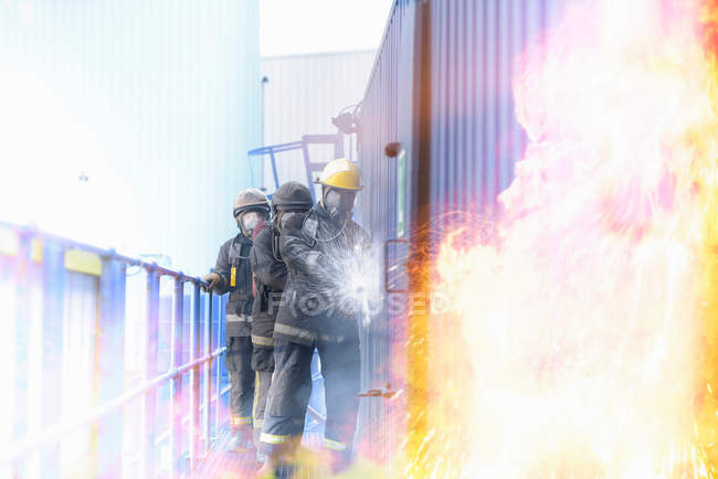 Three firefighters tackling flames in fire simulation at training facility, front view — Stock Photo