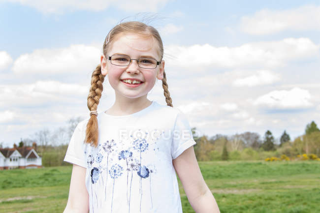 Portrait of redhead girl in spectacles with plaits — Stock Photo