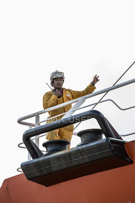 Рабочий, использующий рацию на нефтяной танкерной палубе — стоковое фото
