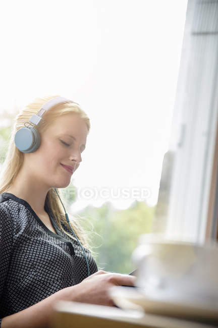 Young woman listening to music with earphones — Stock Photo