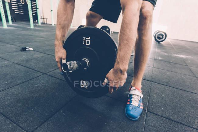 Zugeschnittenen Schuss des Mannes Vorbereitung Langhantel in cross-training Fitness-Studio — Stockfoto