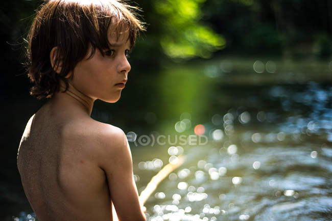 Rear view of boy by water looking away over shoulder — Stock Photo