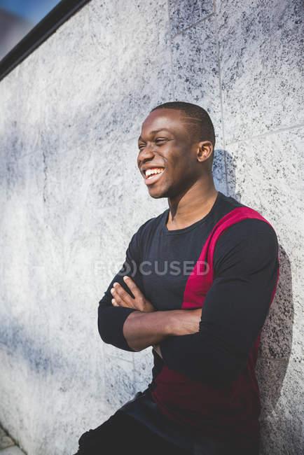 Retrato de jovem homem encostado a parede, braços cruzados, rindo — Fotografia de Stock