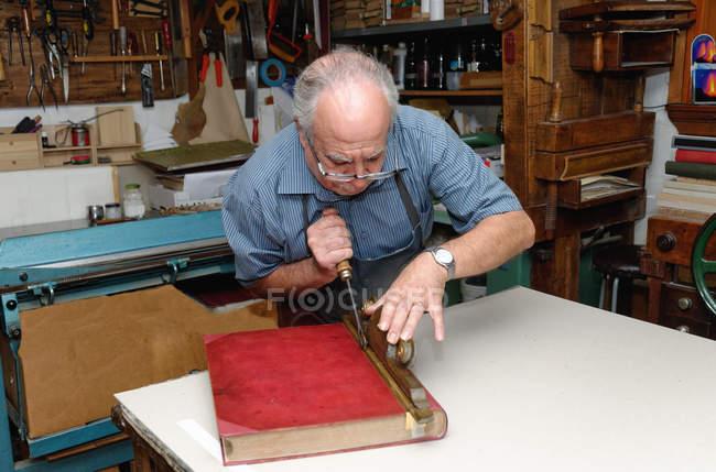 Старший чоловік відновлення книги в традиційних палітурне майстерні — стокове фото