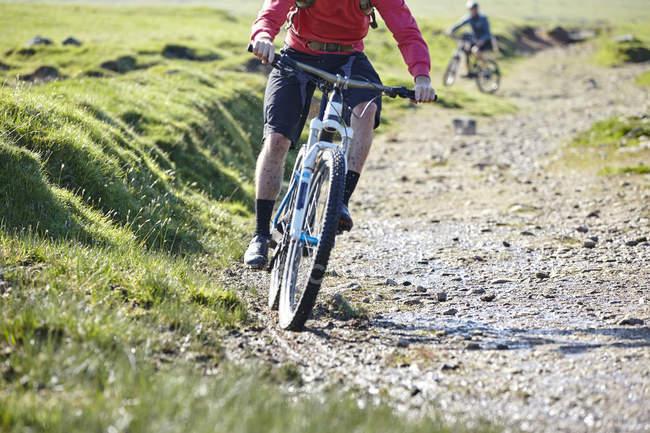 Обрезанное изображение велосипедистов велосипеде вниз грунтовой дороге — стоковое фото