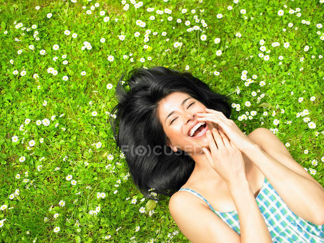 Woman smiling, surrounded by daisies — Stock Photo